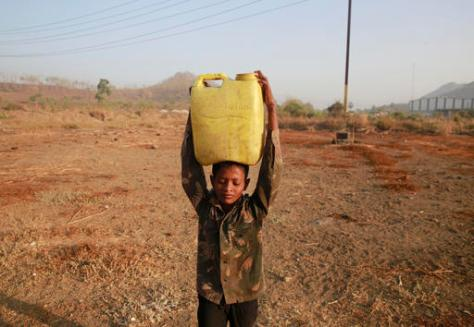 In this April 12, 2016 photo, a boy who migrated from drought hit areas of the western Indian state of Maharashtra, carries water to his family's makeshift hut in Kukse Borivali, 85 kilometres (53 miles) north-east of Mumbai, India. Decades of groundwater abuse, populist water policies and poor monsoons have turned vast swaths of central and western India into a dust bowl, driving distressed farmers to suicide or menial day labor in the cities. (AP Photo/Rafiq Maqbool)